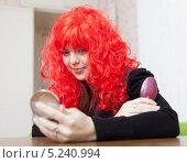 Купить «Девушка в красном парике смотрится в зеркало», фото № 5240994, снято 21 декабря 2012 г. (c) Яков Филимонов / Фотобанк Лори
