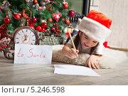Купить «Веселая девочка в новогоднем колпаке около елки пишет письмо Санта Клаусу», фото № 5246598, снято 2 ноября 2013 г. (c) Оксана Гильман / Фотобанк Лори