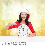 Купить «Счастливая девушка в шапке Санты смотрит на часы и ждет наступления полночи», фото № 5246778, снято 20 октября 2013 г. (c) Syda Productions / Фотобанк Лори