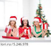 Купить «Счастливые девушки заворачивают новогодние подарки в яркую бумагу», фото № 5246978, снято 20 октября 2013 г. (c) Syda Productions / Фотобанк Лори