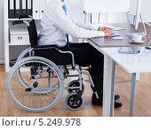 Купить «офисный работник за рабочим столом сидит в инвалидной коляске», фото № 5249978, снято 6 июля 2013 г. (c) Андрей Попов / Фотобанк Лори