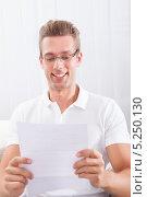 Купить «радостный мужчина что-то читает на листе бумаги», фото № 5250130, снято 6 июля 2013 г. (c) Андрей Попов / Фотобанк Лори