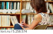 Купить «Young woman studying in library with notepad», видеоролик № 5258574, снято 29 марта 2020 г. (c) Wavebreak Media / Фотобанк Лори