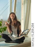 Молодая женщина улыбается мечтая, сидя на подоконнике, закрыв глаза, держит в руках открытую книгу и чашку (2013 год). Редакционное фото, фотограф Ирина Апарина / Фотобанк Лори
