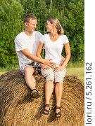Молодая пара сидит на рулоне сена. Стоковое фото, фотограф Rumo / Фотобанк Лори
