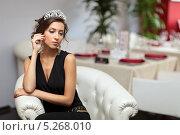 Купить «Задумчивая девушка в черном костюме с диадемой на голове сидит в мягком кресле в интерьере ресторана», фото № 5268010, снято 25 августа 2013 г. (c) Игорь Долгов / Фотобанк Лори