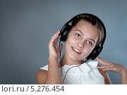 Портрет красивой девушки в наушниках на сером фоне. Стоковое фото, фотограф Римма Зайцева / Фотобанк Лори