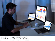 Купить «молодой мужчина работает на компьютерах», фото № 5279214, снято 9 сентября 2013 г. (c) Андрей Попов / Фотобанк Лори