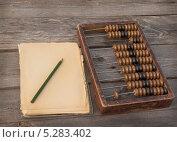 Купить «Ретро-счеты, карандаш и стопка листов старой бумаги на деревянном столе», фото № 5283402, снято 2 ноября 2013 г. (c) Олеся Сарычева / Фотобанк Лори