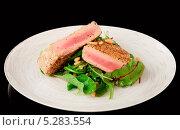 Слегка обжареный стейк из филе тунца на тарелке с кунжутом и овощами. Изолированно на чёрном. Стоковое фото, фотограф Федор Кондратенко / Фотобанк Лори