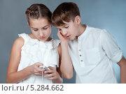 Мальчик и девочка слушают музыку с мобильного телефона. Стоковое фото, фотограф Римма Зайцева / Фотобанк Лори