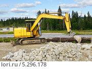 Желтый экскаватор строит дорогу в лесу около озера. Север. Стоковое фото, фотограф Валерия Попова / Фотобанк Лори