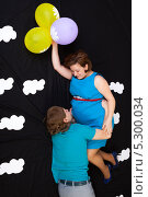Купить «Ожидающие пополнения семьи супруги летят по небу на воздушных шариках», фото № 5300034, снято 28 октября 2012 г. (c) Сергей Дубров / Фотобанк Лори