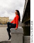 Симпатичная молодая девушка в оранжевой куртке сидит на набережной (2013 год). Стоковое фото, фотограф Юрий Селиванов / Фотобанк Лори