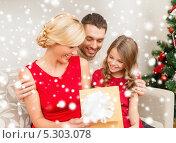 Купить «Счастливые родители и дочка обмениваются подарками на Рождество», фото № 5303078, снято 26 октября 2013 г. (c) Syda Productions / Фотобанк Лори