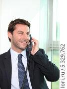 Купить «Улыбающийся бизнесмен звонит по проводному телефону», фото № 5329762, снято 19 мая 2010 г. (c) Phovoir Images / Фотобанк Лори