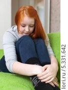 Купить «Расстроенная рыжеволосая девушка сидит на диване, положив голову на колени», фото № 5331642, снято 5 января 2013 г. (c) Яков Филимонов / Фотобанк Лори