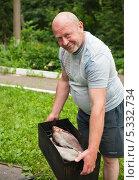 Купить «Мужчина держит коптилку с двумя лещами, готовыми к копчению», эксклюзивное фото № 5332734, снято 22 июня 2013 г. (c) Игорь Низов / Фотобанк Лори