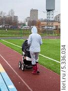 Купить «Женщина осенью гуляет с коляской вдоль футбольного поля», эксклюзивное фото № 5336034, снято 6 ноября 2013 г. (c) Родион Власов / Фотобанк Лори