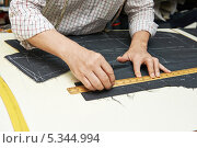 Купить «Портной отмеряет ткань по линейке», фото № 5344994, снято 6 мая 2013 г. (c) Дмитрий Калиновский / Фотобанк Лори