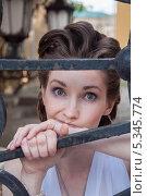 Купить «Девушка в белом со скептическим выражением лица у решётки ворот», фото № 5345774, снято 18 июля 2013 г. (c) Александра Орехова / Фотобанк Лори