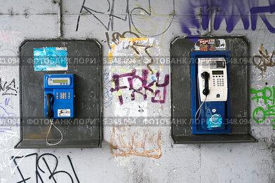 Купить «Уличные телефоны-автоматы на исписанной стене. Чехия», фото № 5348094, снято 20 июля 2019 г. (c) Илюхин Илья / Фотобанк Лори