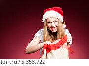 Купить «Веселая девушка в новогоднем колпаке достает подарок из мешка», фото № 5353722, снято 17 июня 2019 г. (c) Игорь Бородин / Фотобанк Лори