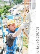 Рабочий штукатурит фасад здания. Стоковое фото, фотограф Дмитрий Калиновский / Фотобанк Лори