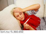 Купить «Заболевшая женщина лежит на диване с градусником», фото № 5360650, снято 22 сентября 2013 г. (c) Andrejs Pidjass / Фотобанк Лори