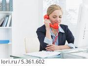 Купить «Female executive using red land line phone at desk», фото № 5361602, снято 28 сентября 2012 г. (c) Wavebreak Media / Фотобанк Лори