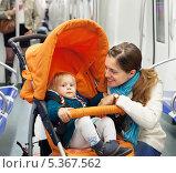 Молодая женщина с ребёнком в коляске едет в метро. Стоковое фото, фотограф Яков Филимонов / Фотобанк Лори