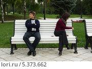 Купить «Курящая девушка и не курящий мужчина сидят рядом в парке на скамейке», фото № 5373662, снято 12 сентября 2013 г. (c) Михаил Иванов / Фотобанк Лори