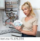 Печальная женщина-домохозяйка подсчитывает деньги на ремонт газового водонагревателя. Стоковое фото, фотограф Куликов Константин / Фотобанк Лори