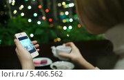 Купить «Девушка листает фотографии на смартфоне за чаем в кафе», видеоролик № 5406562, снято 18 декабря 2013 г. (c) Данил Руденко / Фотобанк Лори
