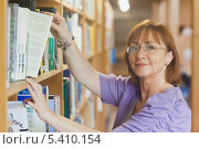 Купить «Mature female librarian taking a book off a shelf», фото № 5410154, снято 28 августа 2013 г. (c) Wavebreak Media / Фотобанк Лори