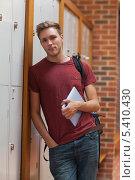Купить «Handsome student leaning against lockers holding tablet», фото № 5410430, снято 29 августа 2013 г. (c) Wavebreak Media / Фотобанк Лори