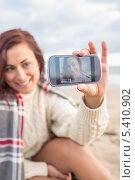 Woman self photographing with smartphone on beach. Стоковое фото, агентство Wavebreak Media / Фотобанк Лори