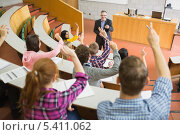Students raising hands with teacher in the lecture hall. Стоковое фото, агентство Wavebreak Media / Фотобанк Лори