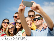 Купить «компания друзей в солнечных очках фотографируется на смартфон», фото № 5421910, снято 31 августа 2013 г. (c) Syda Productions / Фотобанк Лори