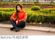 Симпатичная молодая девушка в оранжевой куртке сидит на обочине тротуара. Стоковое фото, фотограф Юрий Селиванов / Фотобанк Лори