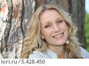 Купить «Улыбающаяся красивая женщина на фоне древесного ствола», фото № 5428450, снято 18 мая 2010 г. (c) Phovoir Images / Фотобанк Лори