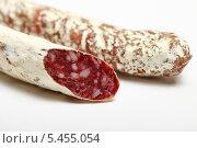 Сырокопченая колбаса на белом фоне. Стоковое фото, фотограф Яна Королёва / Фотобанк Лори