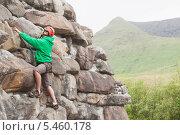 Купить «Focused man climbing a large rock face», фото № 5460178, снято 20 июня 2013 г. (c) Wavebreak Media / Фотобанк Лори