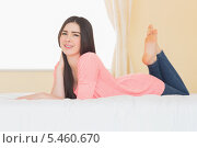 Купить «Content girl looking at camera lying on her bed», фото № 5460670, снято 22 мая 2013 г. (c) Wavebreak Media / Фотобанк Лори