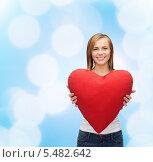 Купить «улыбающаяся девушка держит подушку в форме сердца на голубом фоне», фото № 5482642, снято 5 декабря 2013 г. (c) Syda Productions / Фотобанк Лори