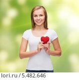 Купить «милая девушка держит пластиковое сердце на зеленом фоне», фото № 5482646, снято 5 декабря 2013 г. (c) Syda Productions / Фотобанк Лори