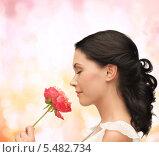 Купить «профиль брюнетки, нюхающей цветок на розовом фоне», фото № 5482734, снято 2 марта 2013 г. (c) Syda Productions / Фотобанк Лори