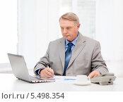 Купить «сосредоточенный пожилой бизнесмен смотрит в экран ноутбука», фото № 5498354, снято 12 октября 2013 г. (c) Syda Productions / Фотобанк Лори