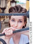 Купить «Портрет девушки у решётки ворот», фото № 5508918, снято 18 июля 2013 г. (c) Александра Орехова / Фотобанк Лори