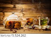 Купить «Стеклянный чайник и чашки с чаем на деревянном фоне», фото № 5524262, снято 21 января 2014 г. (c) Andrejs Pidjass / Фотобанк Лори